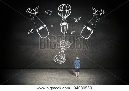 Businesswoman standing with hands behind back against black wall