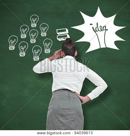 Businesswoman scratching her head against green chalkboard