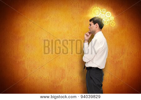 Thoughtful young businessman looking away against orange background