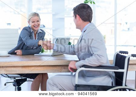 Businesswoman interviewing disabled job candidate in an office