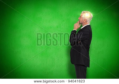 Thoughtful mature businessman posing against green background