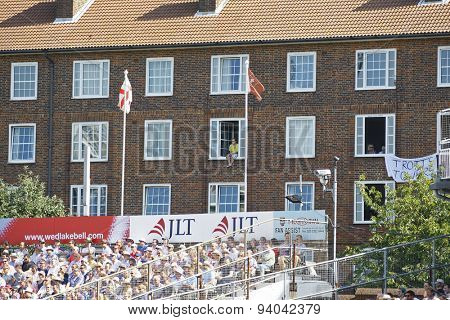 LONDON, ENGLAND - August 21 2013: A cricket fan sits on a window ledge to watch the match on day one of the 5th Investec Ashes cricket match between England and Australia