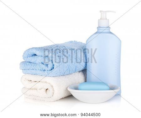 Shampoo bottle and soap with towels. Isolated on white background