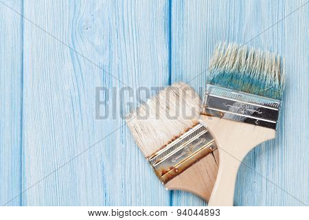 Paintbrush over blue wood. Top view with copy space