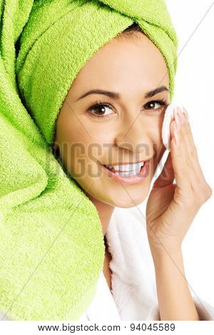 Portrait of a woman in bathrobe removing makeup.