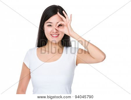 Asian woman with ok sign gesture on her eye