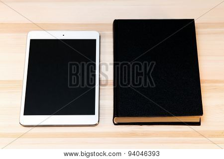 book and tablet on the table