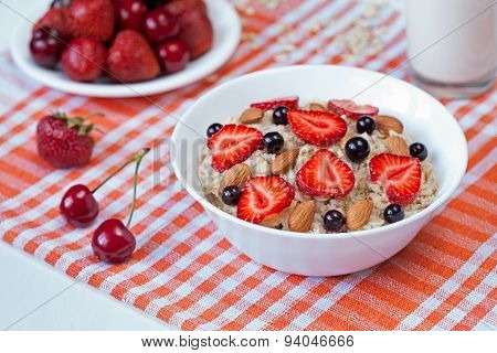 Oatmeal porridge helathy breakfast with strawberry, cherries, milk and almond nuts in white dish on