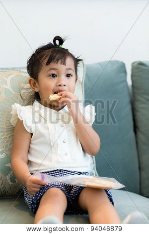 Lovely girl having finger food at home
