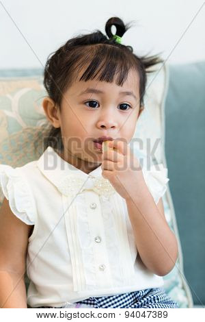 Cute girl having finger food at home