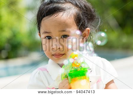 Girl play with bubble blower at outdoor