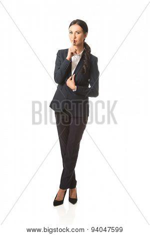 Full length businesswoman making silent sign.