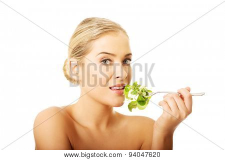 Happy nude woman eating lettuce