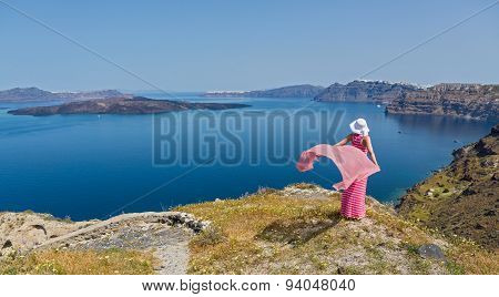 Woman Stands On The Edge Of A Cliff. Greece, Santorini