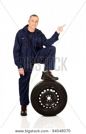 Repairman with leg on a tire pointing to the left.