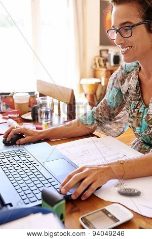 Mature woman busy doing book keeping from her home