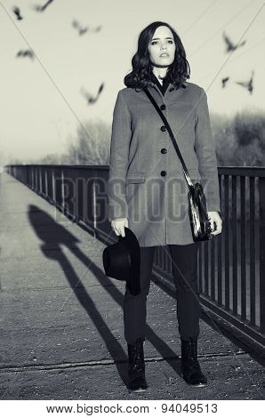 Beautiful Young Fashionable Lady Standing On Bridge At Sunrise While Birds Are Flying Over Her Head