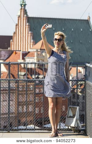 Beautiful young blond woman doing self-portrait on smartphone from the observation deck at Warsaw.