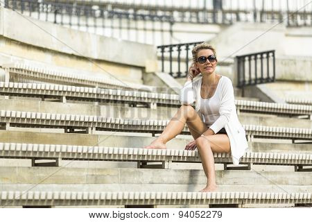Young beautiful blondie woman sitting on benches in the stadium.