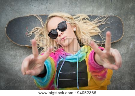 Blond teen skater girl giving peace sign