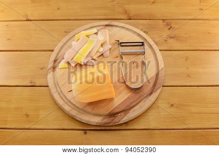 Butternut Squash With A Vegetable Peeler On A Chopping Board