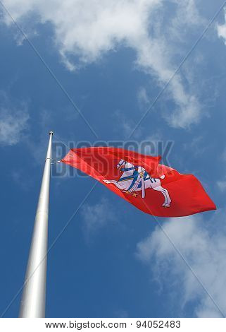 Old lithuanian flag in blue sky background