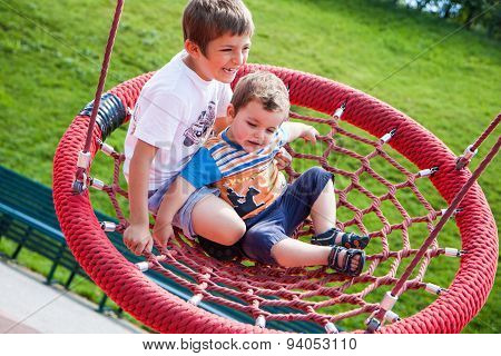 Two Children Fun On Swing Round