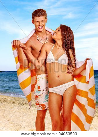 Couple with towel at  beach. Summer outdoor.