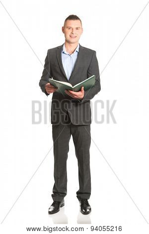 Smiling handsome businessman reading his note book.