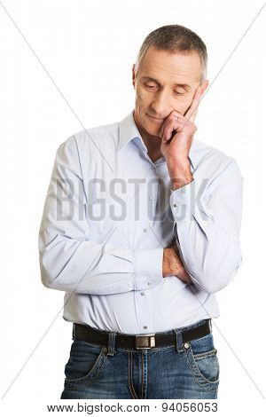 Pensive mature man touching chin.
