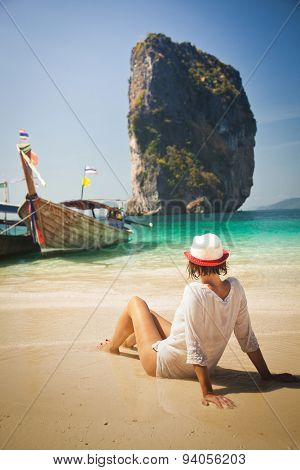 Woman sitting on Tropical beach relaxing and watching longtail boats, Andaman Sea, Thailand