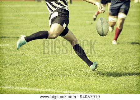Rugby player kicking hard the oval ball - sports concept, retro style photo
