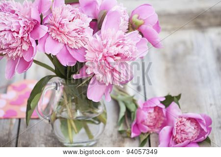 Pink peonies in vase on wooden floor - retro styled photo