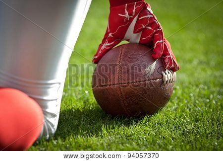 american football playerl kneeling on stadium, out of focus players in the background