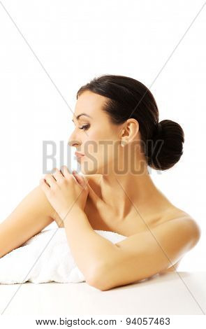 Beautiful spa woman with rolled towel on the desk.