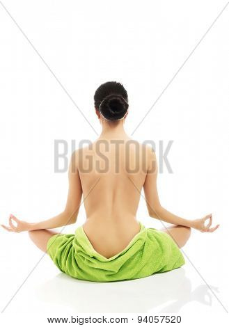 Serene woman excercising yoga wrapped in towel.