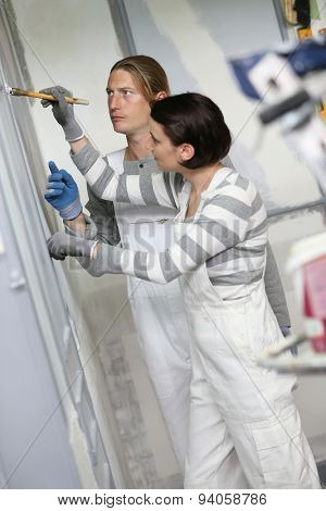 Young woman painter in professional training, teacher controlling work