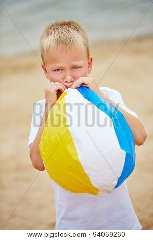 Boy in summer inflating a beach ball with his mouth