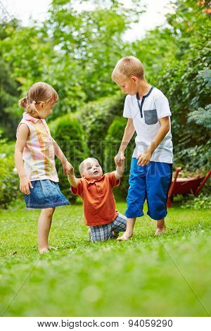Two helpful children helping baby learning to walk in a garden in summer