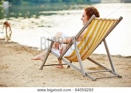 Smiling young woman relaxing on beach in deck chair in summer