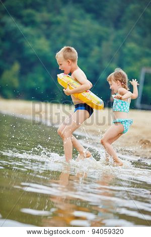 Two happy children bathing together in a lake in summer