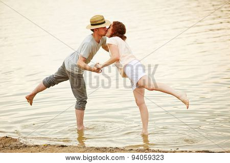 Couple in love kissing in water of lake in summer