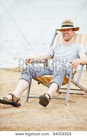 Happy man sitting relaxed in deck chair on beach in summer