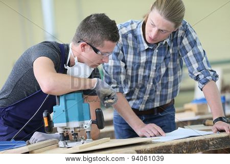 Apprentice with adult in carpentry school working on wood