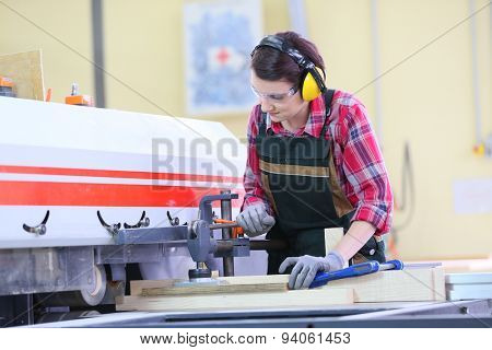 Young carpenter using electric sawing machine