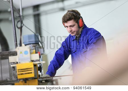 Young man in metallurgy workshop working on machine