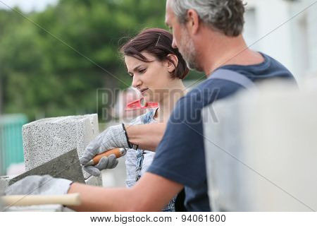 Mason with trainee in construction, building wall