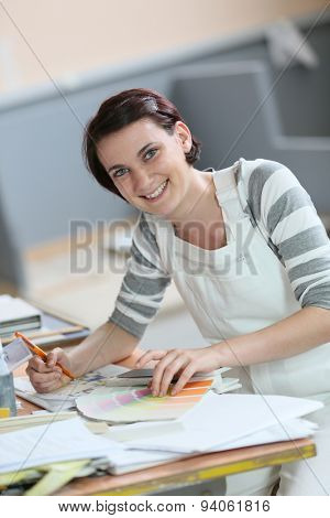 Young woman painter sitting at working table