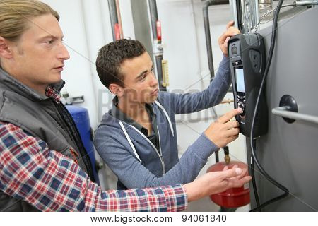 Young man in professional training measuring heat pump temperature