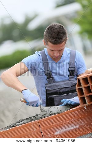 Young brick layer working outside on brick wall construction